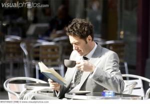 カフェで子^ひーを読みながら読書する男性